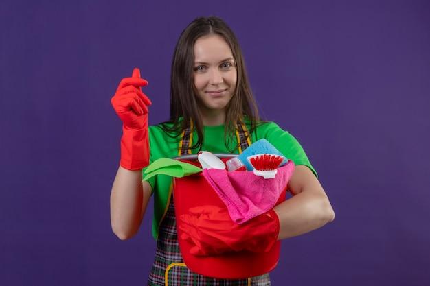 Pulizia giovane donna che indossa l'uniforme in guanti rossi in possesso di strumenti per la pulizia che mostra il gesto di contanti sulla parete viola isolata