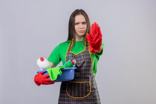 Pulizia giovane donna che indossa l'uniforme in guanti rossi che tengono gli strumenti di pulizia che mostrano il gesto di arresto sul muro bianco isolato