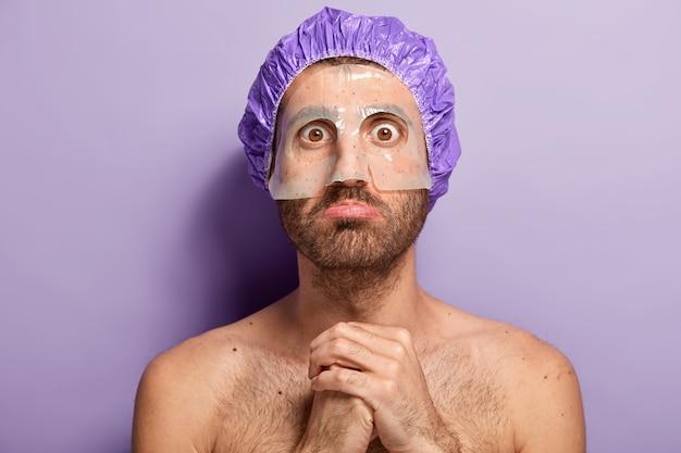 清潔さと美容トリートメントのコンセプト。ショックを受けた真面目な男性が美容師を訪ね、手をつないで、マスクを顔につけてポーズをとる