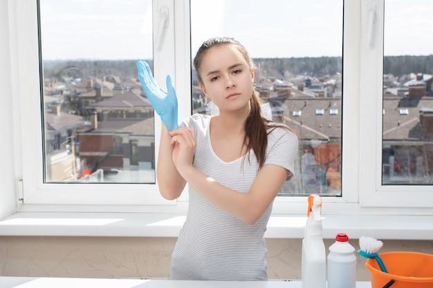 Чистота и гигиена в доме. молодая девушка надевает резиновые перчатки для уборки