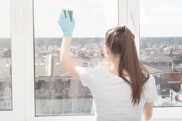 Cleanliness and hygiene in the house. a young girl in an apartment washes a window with a sponge
