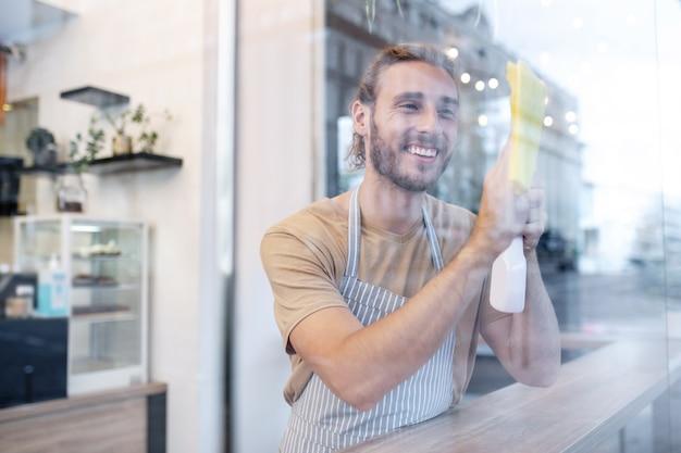 清潔さ、透明性。きれいな表面を拭くカフェでガラスの後ろに立っているエプロンで若い男を喜んで陽気な笑顔
