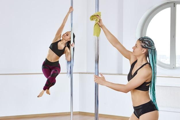 Очищает оборудование для танцев на пилоне, изящная сексуальная женщина вытирает стержень салфеткой из микрофибры