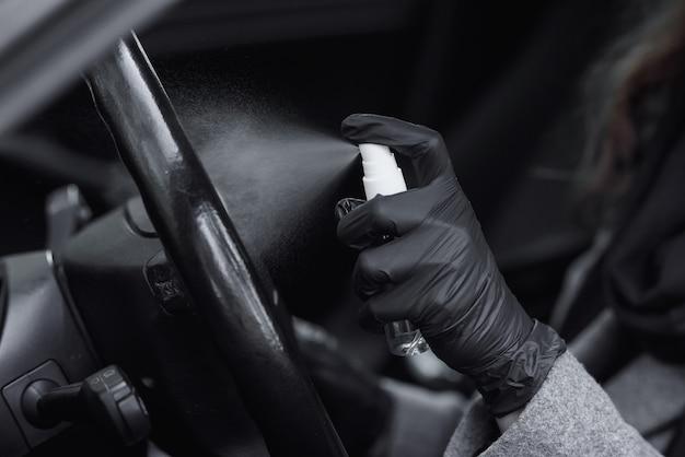 車の内部をクレンジングし、消毒液をスプレーします。ウイルス病から保護するために車内を消毒するゴム製保護手袋を着用した手