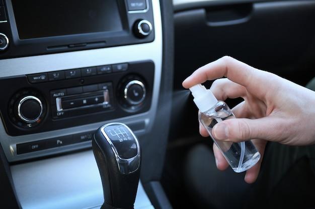 車内を消毒液で洗浄します。車のハンドルとハンドルの消毒。コロナウイルス、covid-19保護。車内の消毒