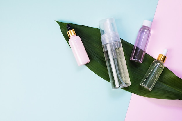 Cleansing foam or micellar water and a variety of moisturizing serums on a pastel background and palm leaf