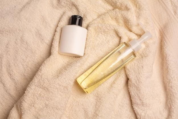 トイレのしわくちゃのタオルの上に横たわるクレンジングオイルと酵素パウダー。コピースペース