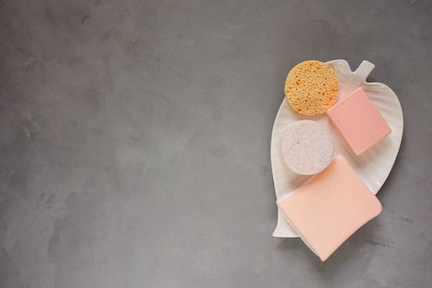 Губки и мыло чистящие средства на белой тарелке в форме листа серого цвета