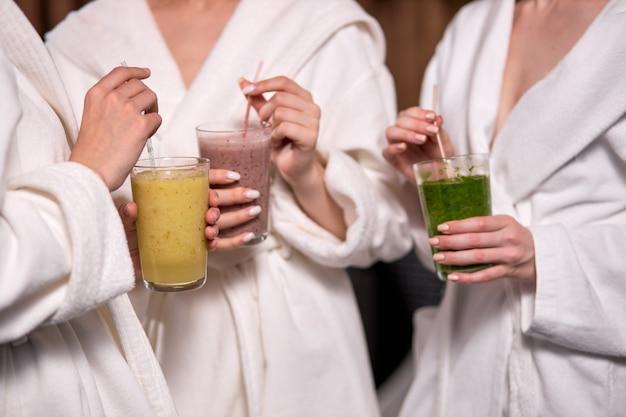 독소의 몸, 스파 살롱의 여자 친구, 목욕 가운 착용. 웰빙 살롱에있는 세 명의 여성이 흰 가운을 입고 비타민 칵테일을 마시고 있습니다. 클로즈업, 안경 손에 초점