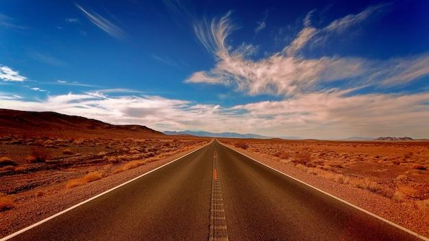 Chiara strada di cemento nero sotto cieli bianchi e blu