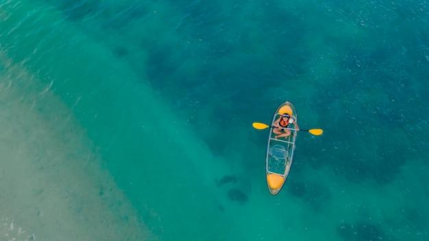 투명한 카약이 떠 있는 맑고 푸른 바다, 보트에 구명조끼를 입은 사람