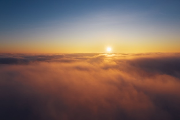 Clear blue sky above the clouds during sunrise. dramatic cloudscape at dawn.