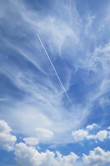 夏の間は白い雲と飛行機雲のある澄んだ青い空