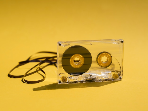 Clear broken cassette tape on yellow background