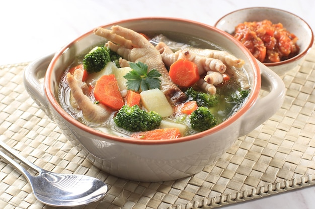 Clear chicken feet (claw) soup with potato, broccoli, and carrots. served on marble table in brown bowl with sambal