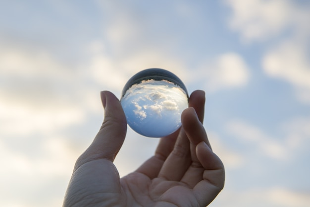 A clear crystal ball is reflecting the scene behind in the inverted view