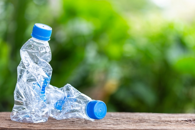 Clear empty plastic bottle on wooden table or counter with green nature light blur background