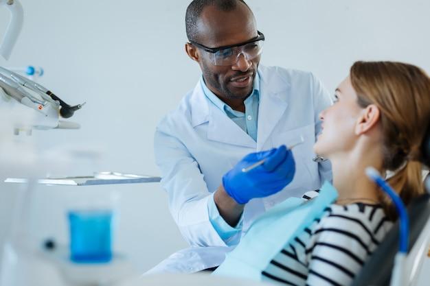 명확한 설명. 그가 그녀에게 치료 프로토콜을 설명하는 동안 그녀의 남성 치과 의사를주의 깊게 듣고 매력적인 젊은 여자