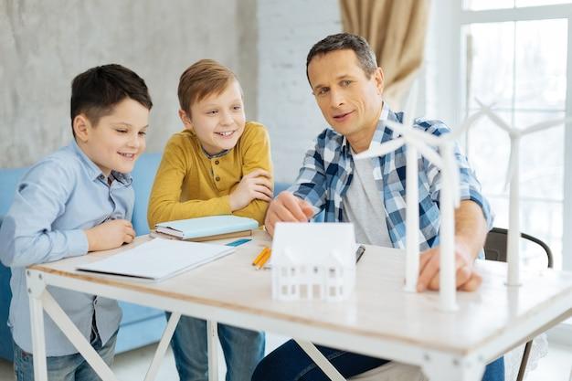Четкое объяснение. веселый приятный молодой отец сидит за столом со своими двумя сыновьями и объясняет им устройство ветряных турбин.