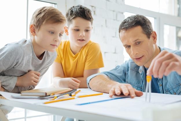 明確な説明。男の子が彼に注意を払っている間、コンパスで距離を測定する方法を息子に示す楽しい若いエンジニア