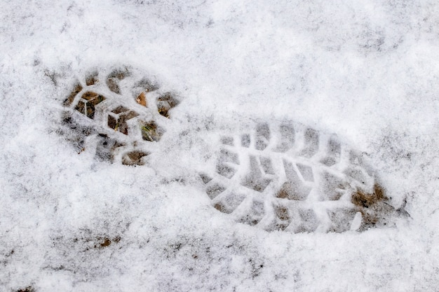 Clear footprint of shoes on white snow