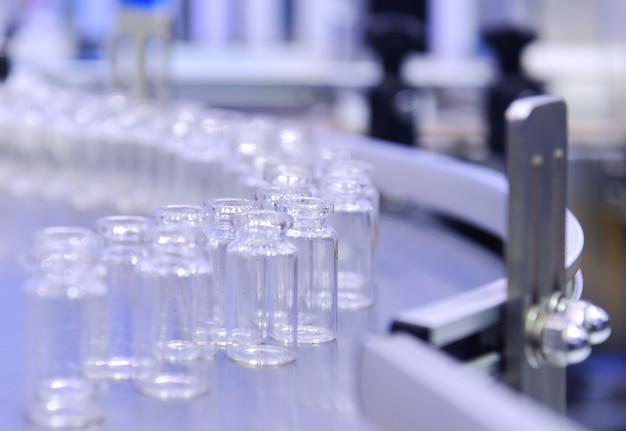 Прозрачные стеклянные флаконы для транспортировки флаконов с вакциной на автоматизированных конвейерных системах для фармацевтики.