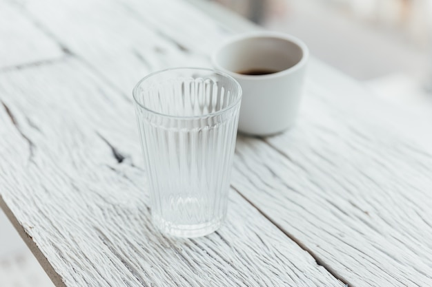 Clear glass and a cup of coffee on white painted wooden table.