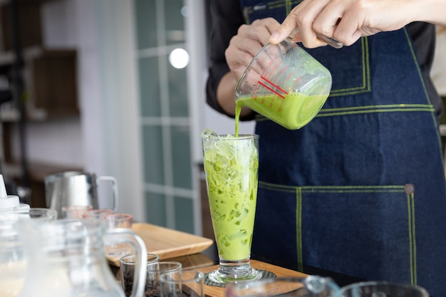 A clear glass of iced pure japanese matcha or green tea menu by barista in the coffe shop.