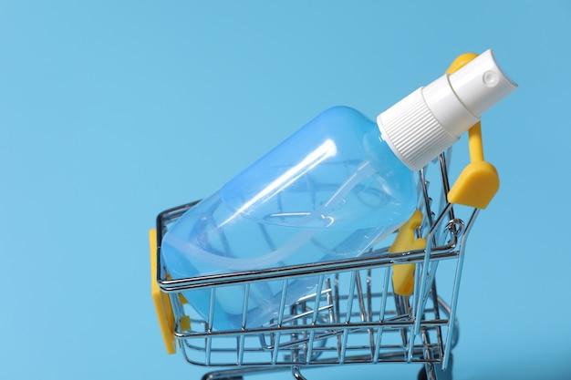 Ясное дезинфицирующее средство для рук в ясной бутылке насоса изолированной на голубой предпосылке. дезинфицирующее средство для рук используется для уничтожения микробов, бактерий и вирусов