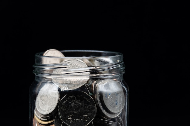 Clear jar full with thai baht coin on black background