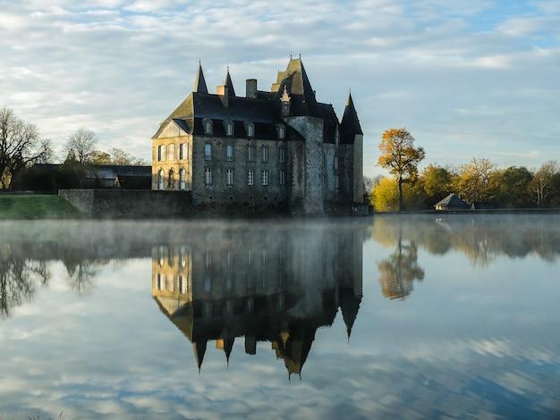 秋の曇り空を背景に巨大な城が映る澄んだ湖