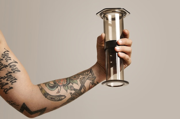 Clear light gray aeropress with reflections held by a tattooed young man, close up portrait