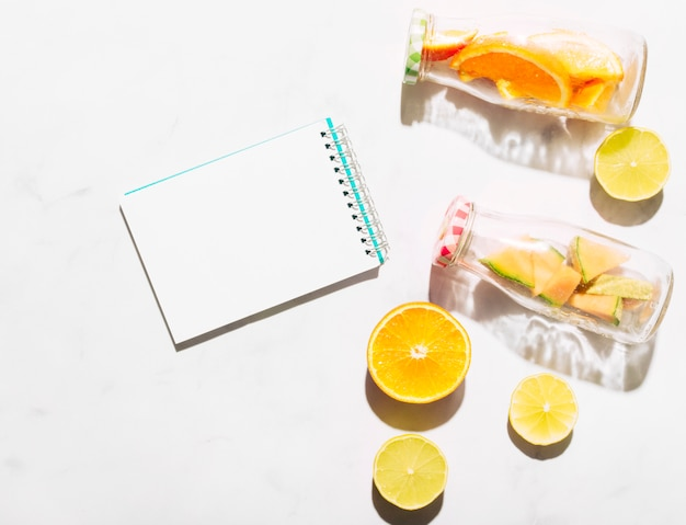 Clear notebook lime orange and glass bottles with cut ​​citrus