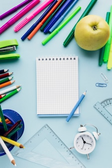 Clear notebook surrounded by bright stationery, clock and apple on blue background