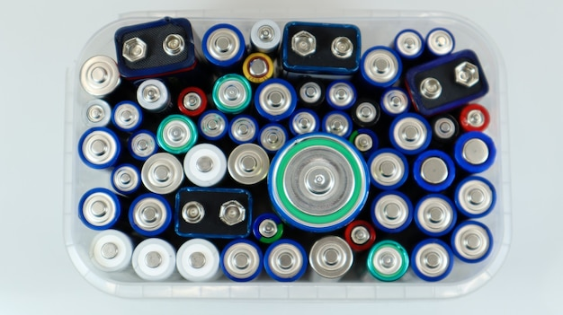 Прозрачный пластиковый ящик, полный использованных бытовых щелочных и литий-ионных батарей типа аа, собранных для переработки в специальные мусорные баки. переработка и проблемы экологии. вид сверху.