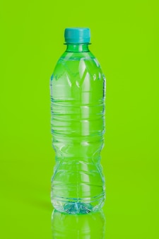 Clear and pure mineral water on a bright green background