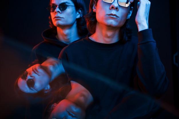 명확한 반사. 쌍둥이 형제의 초상화입니다. 네온 불빛이있는 어두운 스튜디오에서 촬영 한 스튜디오