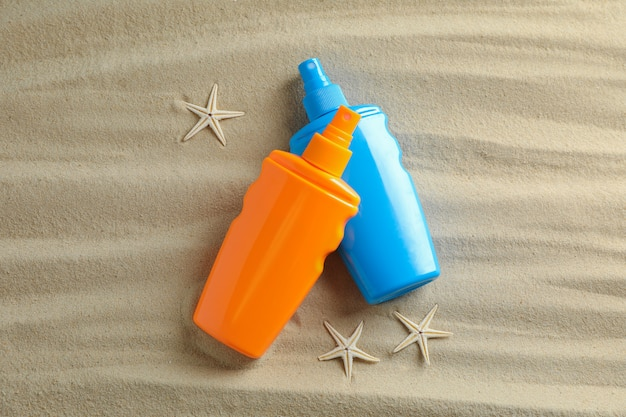 Clear sea sand with starfish and sunscreens, space for text. summer vacation background