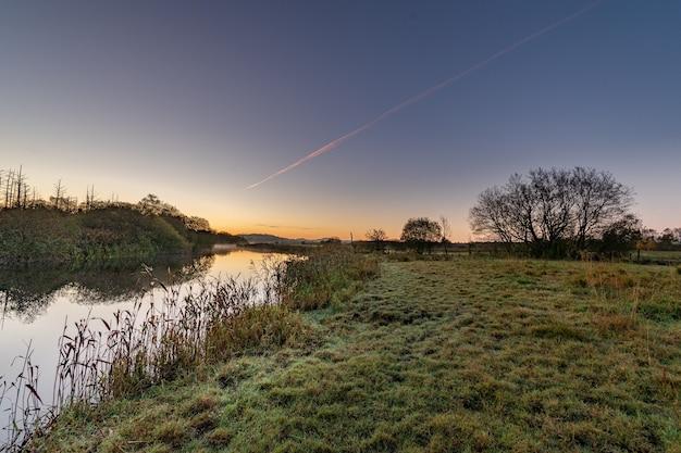 Утро ясного неба на реке инни с отражениями неба, деревьев.