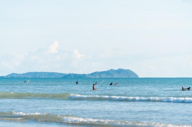 Чистое небо, море, серфер в воде, ожидание волны / пляж для серфинга / летние занятия