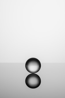 表面に反射するスタジオの背景に分離された透明なクリスタルガラスのボール。