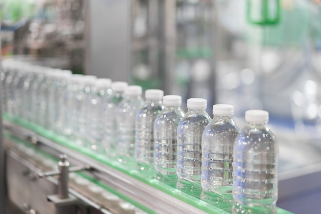 Clear water bottles transfer on conveyor belt system.