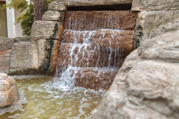 Clear water flows through an artificial waterfall cascade