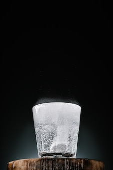 Чистая вода в стакане с витамином с, крупный план, темная стена с копией пространства, выборочный фокус. вода закипает от растворения шипучей таблетки. прием витаминов, профилактика здоровья