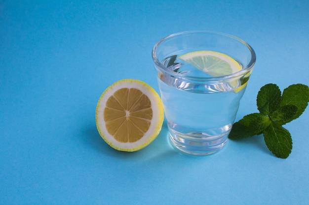 青い背景のガラスにレモンと澄んだ水