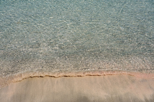 Clear waves and colorful sand on tropical sandy beach in crete greece.
