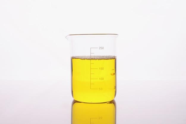 В стакан наливают прозрачную желтую жидкость.