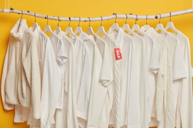 노란색 배경 위에 절연 옷걸이에 흰색 옷의 정리 세일. 여성을위한 패션 의류 선택.