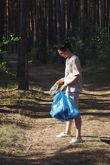 재활용 불가능한 플라스틱 쓰레기의 숲을 없애고 있습니다. 장갑을 끼고 있는 어린 소녀가 가방에 쓰레기를 수집합니다. 생태 재해로부터 환경을 구합니다. 자원 봉사자, 환경 운동가 개념.