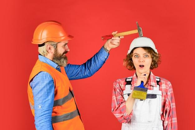 명확하게 설명하십시오. 이해하기 쉬운 개념. 부부가 함께 아파트를 개조합니다. 남자와 여자는 안전 헬멧을 착용합니다. 집에서 수리를 하는 커플. 홈 리노베이션. 문질러. 망치로 머리를 두드리는 커플.